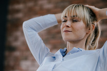 Businesswoman Relaxing In Office, With Hands Behind Head