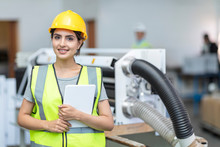 Portrait Of Smiling Female Technician With Tablet