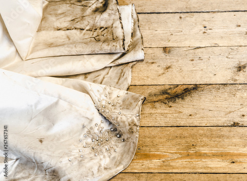 Detail view of beautiful white wedding dress train after outdoor wedding in rainy day on wooden board background Fototapeta
