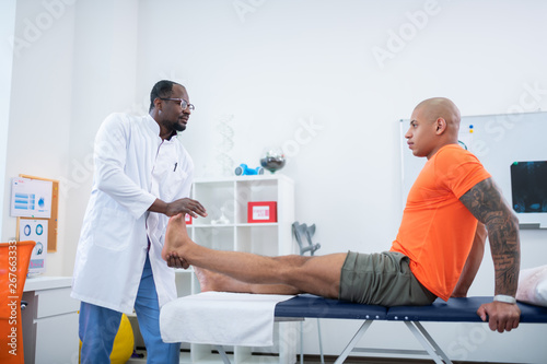 Strong sportsman listening to physical therapist attentively Фотошпалери