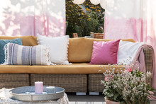 Colorful Pillows On Rattan Sofa On The Terrace With Flowers, Painted Drapes And Candles. Real Photo