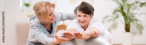 Fototapeta Panorama capture of pilates instructor helping senior woman to stretch on the exercising ball obraz