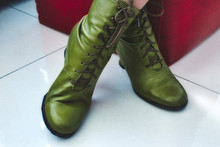 A Pair Of Green Leather Women's Boots With Shoelaces And Heels