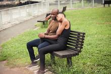 Girlfriend Resting On Boyfriend's Shoulder While Sitting In Park