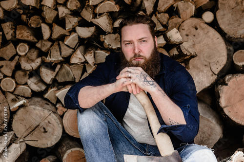 Canvastavla Brutal man with a beard dressed in casual clothes with tattoos on his hands hold