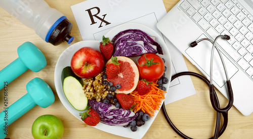 Fototapeta Prescription for good health overhead with stethoscope, healthy fresh food and exercise equipment. obraz