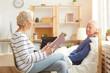 Leinwandbild Motiv Side view portrait of elderly couple enjoying retirement, focus on wife reading book aloud to white haired senior man lying on bed in sunlit apartment