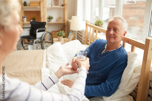 Fotografia Portrait of white haired senior man lying on bed and taking glass of water hande