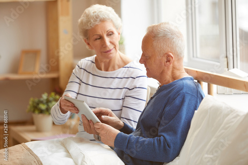 Portrait of modern senior couple using digital tablet sitting on bed in sunlight Wallpaper Mural