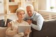 Leinwandbild Motiv Portrait of modern senior couple using digital tablet  at home lit by sunlight, copy space