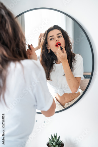 Young woman applying lipstick looking at mirror Canvas Print