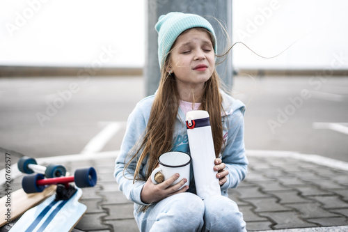 Valokuva  A girl in a blue sweater and hat was riding a longboard and sat down on the curb to drink hot tea from a thermos