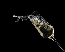 Glass Of Fizzy Champagne On Black Background, Closeup
