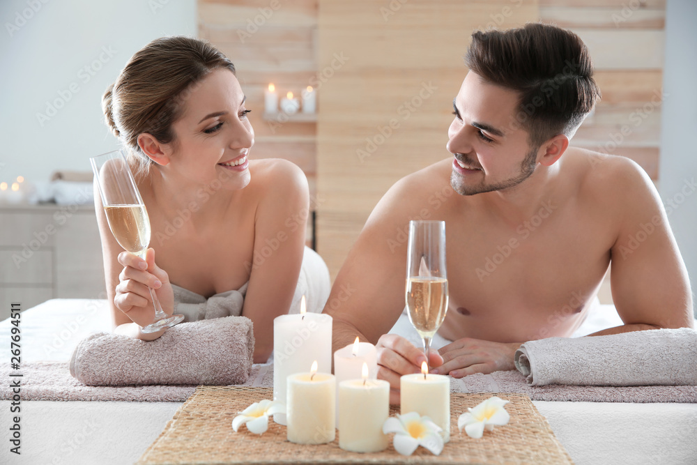Fototapeta Romantic young couple with champagne in spa salon