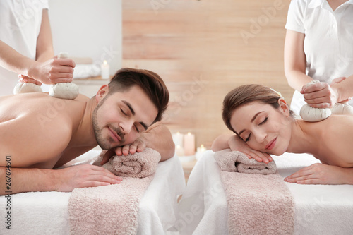 Romantic young couple enjoying herbal bag massage in spa salon