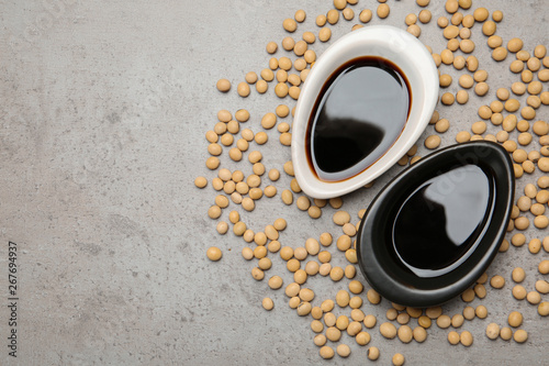 Fototapeta Dishes of soy sauce and beans on grey background, flat lay. Space for text obraz