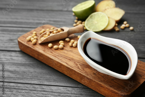 Fototapeta Board with dish of soy sauce and beans on table obraz