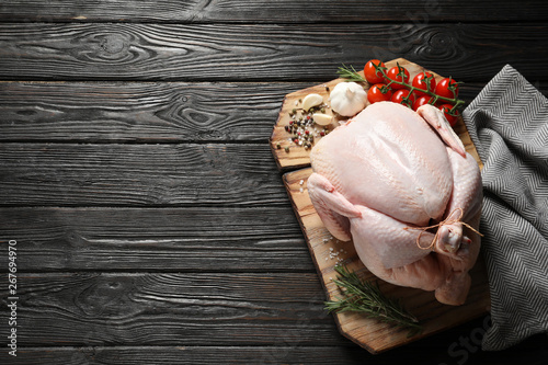 Obraz na płótnie Board with raw turkey and ingredients on wooden background, top view