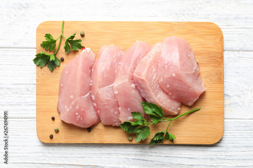 Cuadros en Lienzo Board with cut raw turkey fillet and parsley on white wooden background, top vie