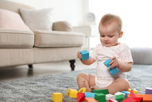 Cute Baby Girl Playing With Building Blocks In Room. Space For Text