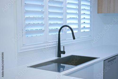 Fototapeta Open plantation shutters and black kitchen sink mixer tap.