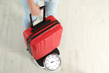Woman Weighing Suitcase Indoors. Space For Text