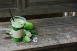 Green apple smoothie in glass and kale leaves on wooden table - 267712568