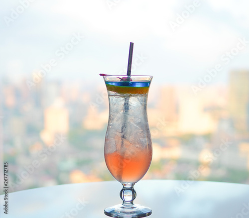 Colorful cocktail decorated with fruits near window cityscape view as background