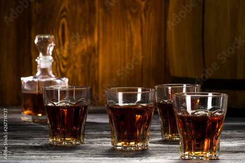 Poster de jardin Bar strong alcoholic drinks in glasses, cognac and brandy in decanters stand on an oak barrel
