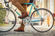 Leinwandbild Motiv Young stylish businessmango to work on his sport retro bike in s