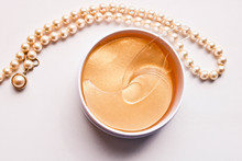 Set Of Golden Anti Aging Eye Patches In The Plastic Jar And Pearl Necklace.