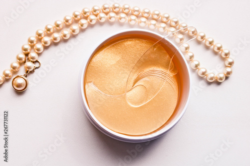 Fotografía Set of golden anti aging eye patches in the plastic jar and pearl necklace