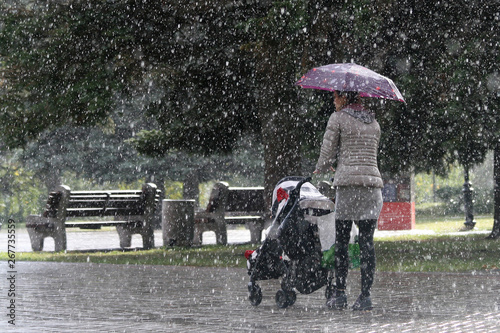 Платно A young mother rolls a stroller with a child in the autumn rain under the umbrel