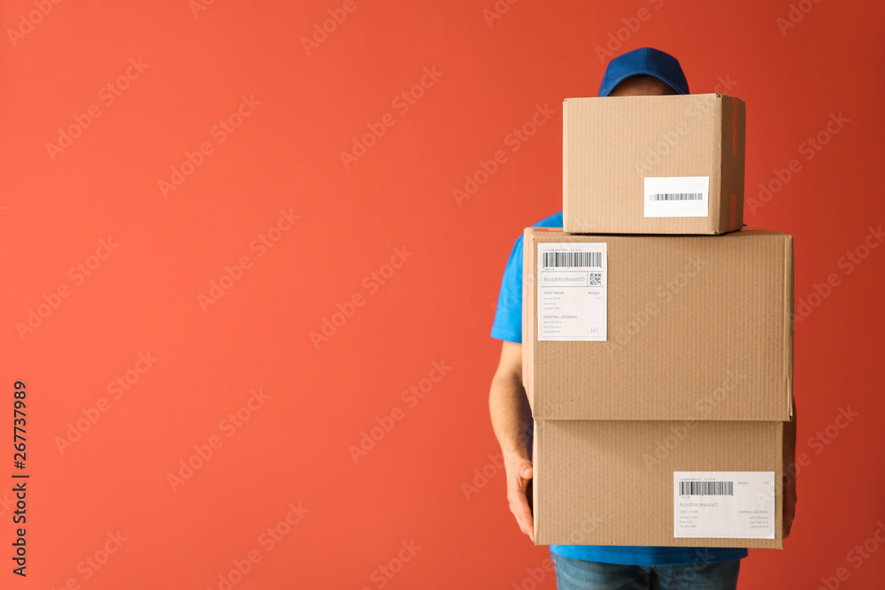 Fototapety, obrazy: Delivery man with boxes on color background