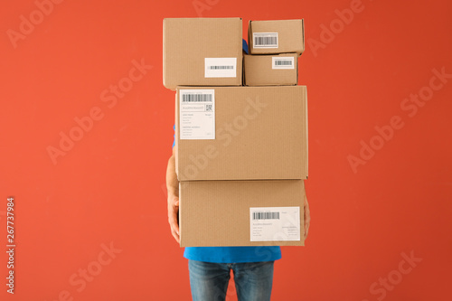Obraz Delivery man with boxes on color background - fototapety do salonu