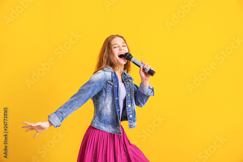 Valokuvatapetti Teenage girl with microphone singing against color background