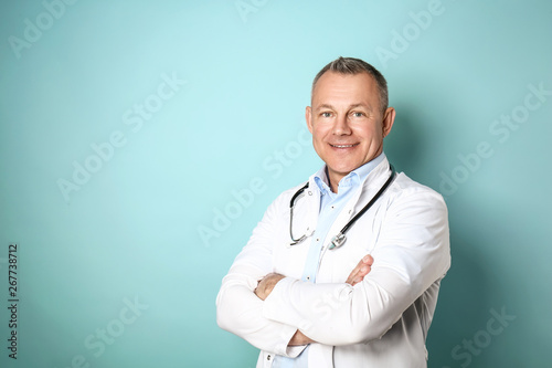 Fotografiet Handsome middle-aged doctor on color background