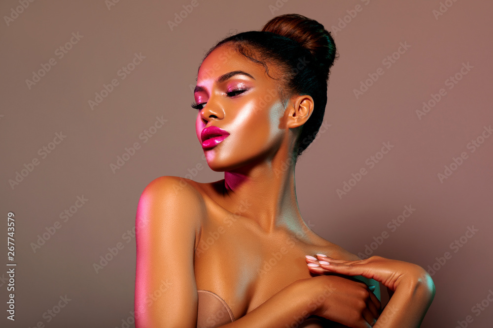 Fototapeta Beauty portrait fashion girl with color lighting filters. Beauty girl face close up. Closeup African American woman with copy space. neon light blue and pink color. - image.