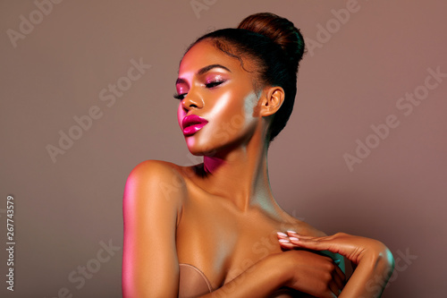 Fototapeta Beauty portrait fashion girl with color lighting filters. Beauty girl face close up. Closeup African American woman with copy space. neon light blue and pink color. - image     obraz