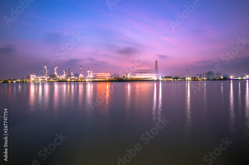 Fototapeta The blurred background of nature along the river, with views of the cargo ship, oil refinery, sunrise and beautiful sky in the morning obraz na płótnie