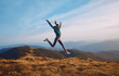 Leinwanddruck Bild - Happy woman hiker jumping on mountain ridge on blue cloudy sky and mountains background. Travel and active lifestyle concept.