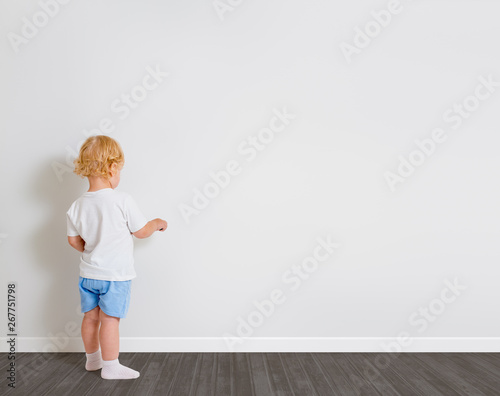 Valokuva  Baby boy drawing on wallpaper standing back to camera