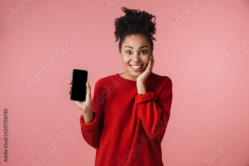 Amazing young african woman posing isolated over pink wall background showing display of mobile phone.