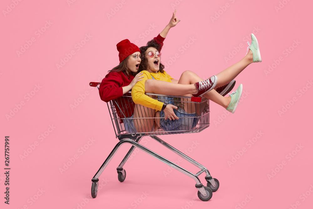 Fototapeta Friends taking part in shopping trolley race