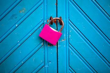 Candado fucsia sobre puerta azul