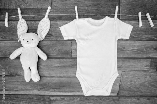 Top view white baby bodysuit on a clothesline with teddy hare on a wooden background Canvas Print
