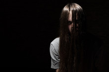 Portrait Of Young Teenager Brunette Girl With Long Hair In The Gothic Style On A Black Background With Copy Space