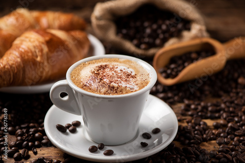 Slika na platnu A cup of cappuccino with coffee bean as background.