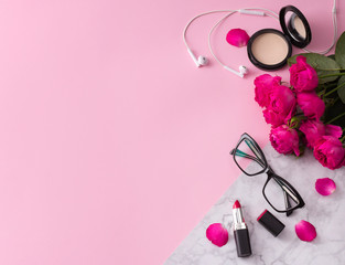 Obraz na płótnie Canvas Cosmetics, makeup brushes, lipstick, powder and glasses with flowers on trendy pink marble background top view