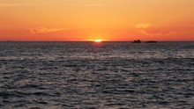 Last Sliver Of Sun Disappears Below Horizon At Sunset Over Ocean. Cargo Container Ship In The Distance.